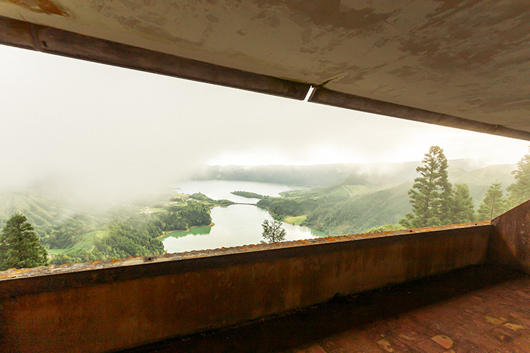 A lake and trees in the background, and a shabby ceiling and floors in the foreground - the views from an abandoned veranda in the Monte Palace Hotel.