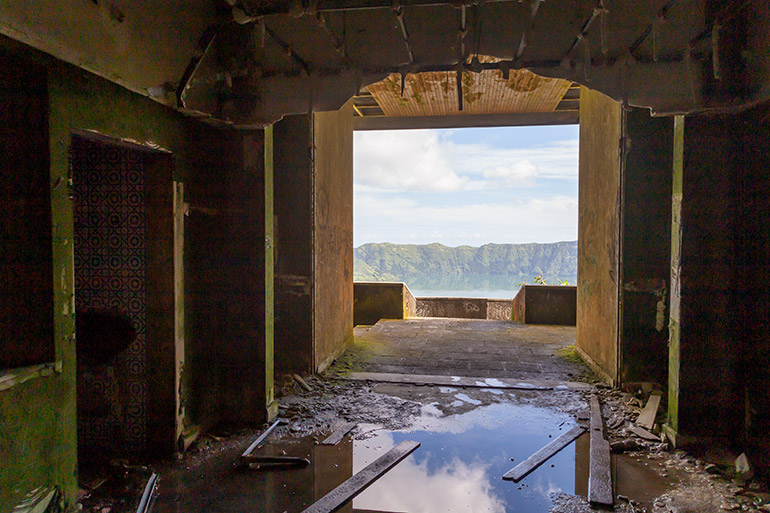 Inside the ruined hotel, shabby walls and ceilings, and a big puddle on the floor, surrounded by construction supplies.  Clouds reflect in the puddle and through an opening in the wall, mountains appear in the distance.