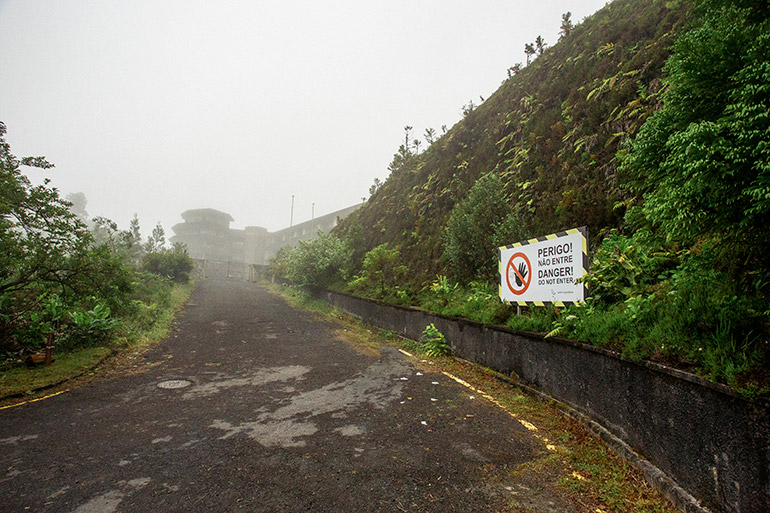 """A driveway leading up to a large hotel in the distance.  In proximity a sign that says """"warning, danger."""""""