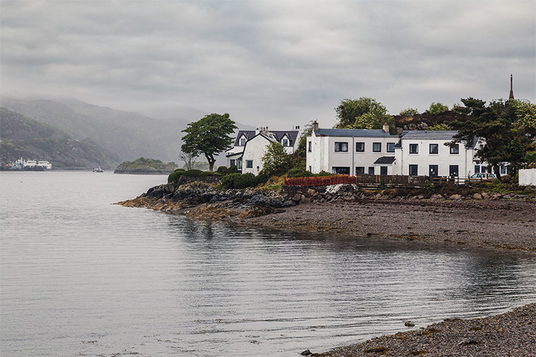 A pretty white series of two story homes set close to a dark sand beach.  Water in the foreground, mountains in the background, cloudy skies overhead.  Trees burried amongst the homes. Things to do on the Isle of Skye - Kyleakin village