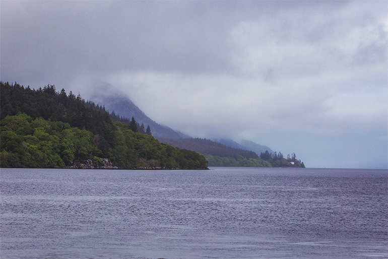 A large smooth lake in the foreground and hills with trees in the background, cloudy sky hangs over the trees covering some of them in a thick layer of mist.