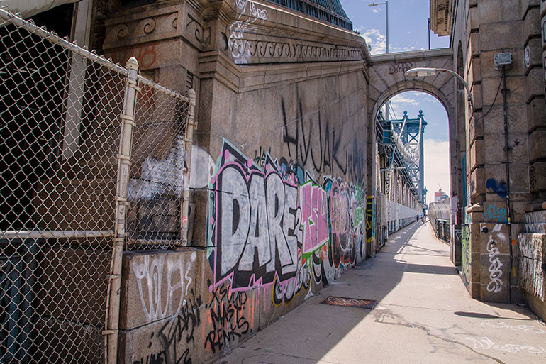 Graffiti painted on the internal structure of the Manhattan bridge.  A pedestrian walkway to the right of the bridge and two towers of the bridge can be seen in the distance.