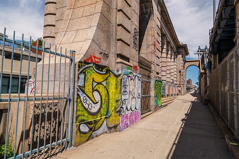 Bright graffiti covers the Manhattan Bridge, the internal structure of the Manhattan bridge with towers.