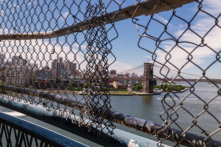 A hole in cut in the fence on the Manhattan bridge, and through the hole one of the towers of the Brooklyn bridge.