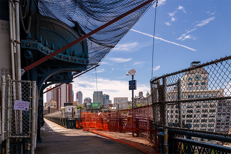 """A construction zone on the Manhattan bridge.  An open pedestrian walkway protected by a hanging netting ad caution signs.  Sign closes to the camera says """"proceed with caution."""""""