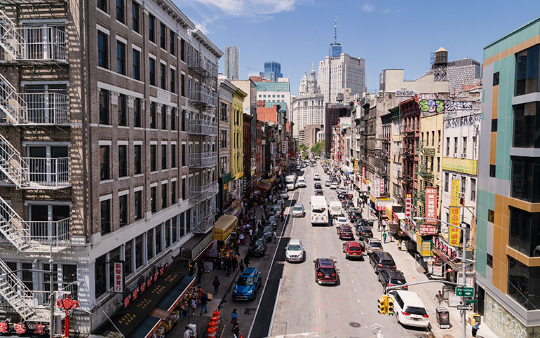 A view of Chinatown as seen off the Manhattan Bridge.  A road in the middle of the picture, on the left and ride sides of the road signs in Mandarin and in the foreground large buildings and freedom tower.  The shot is taken from above the shorter buildings.
