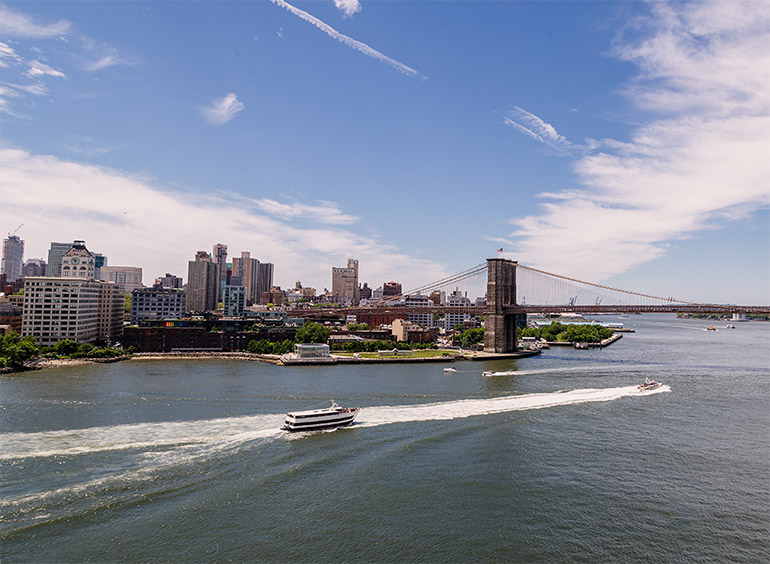 Two towers of the Brooklyn bridge, a view of downtown Brooklyn including mid sized office and residential buildings. Two boats pass in the river below leaving water trails.