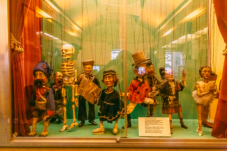 Medium sized marionettes with ropes attached, 12 figurines including a skeleton, a ballerina, a musician, a soldier, and more.