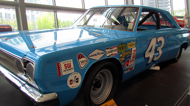 An image of a classic car decorated with various company logos, including good year and penner.  The number 43 on the side.  The car is standing in a glass showroom and in bright daylight.