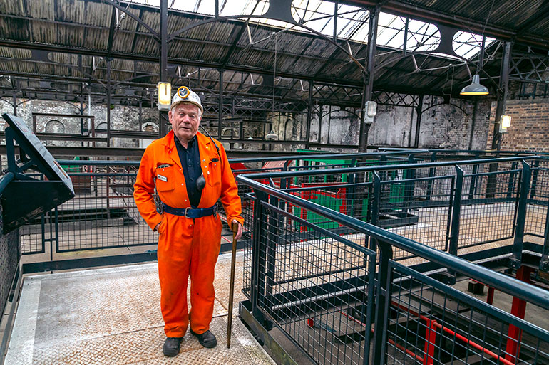Former mine, industrial location, a man in a bright jumpsuit, wearing a headlamp and holding a walking stick.