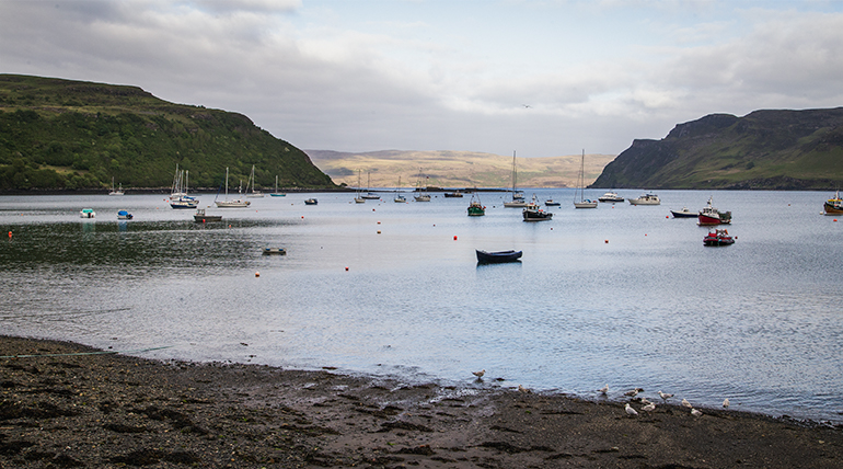 Beach and ocean with small fishing boats, mountains in the background, sun is setting.  Things to do on the Isle of Skye - Portree.