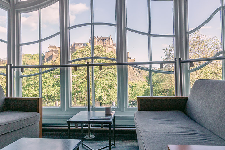 Prince Street Starbucks - Things to do in Edinburgh - two couches and a coffee table between them with a cup of coffee, the views of Edinburgh Castle through a large window in the background.
