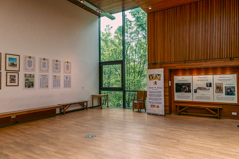 A modern, clean meeting hall, with a large window and trees outside.  8 pieces of artwork on the walls.
