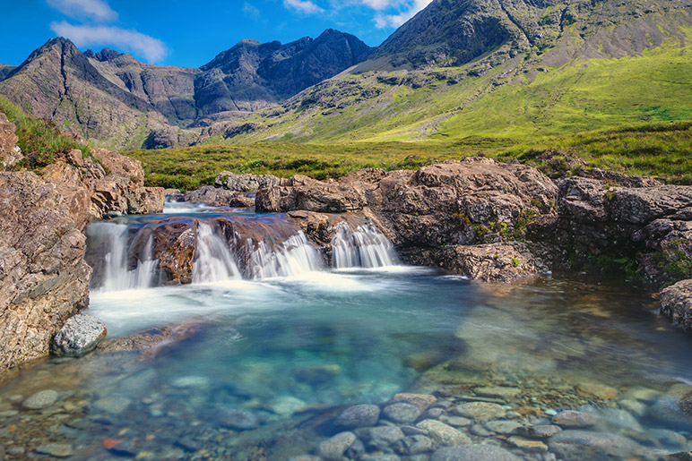 A crystal clear small waterfall drops into clear water beneath, mountains in the background, a bright and sunny day.  Things to do on the Isle of Skye - Fairy Pools