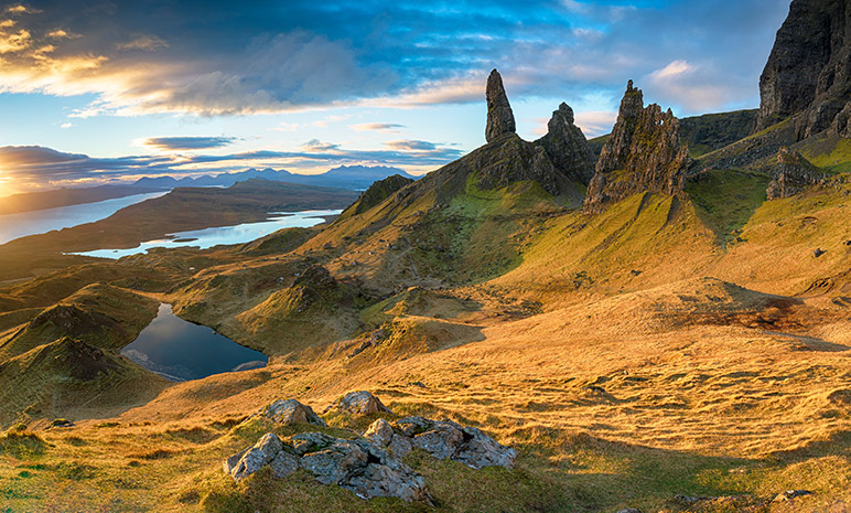 The isle of skye old man of storr, a series of sharp rocks that stick out of mountains.  in the background water and sky, in the foreground yellow grass.  Things to do on the Isle of Skye - Storr