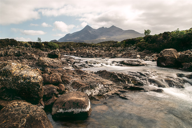 The highalnds in Scotland, a mountain in the background, a running water stream, rocks and low shrubs covered with leaves.  Incredible things to do on the Isle of Skye.