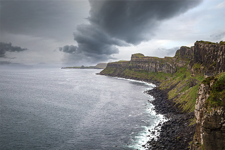 Kilt Rock on the Isle of Skye.  Enormous mountain cliff stretches into the horizon.  On the right endless water and above angry clouds.  In sports, the cliffs are covered with green grass.