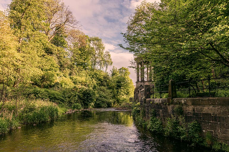 Unique things to do in Edinburgh - Water of Leith.  A water stream lined with green leafy trees, and a small old structure in the background.
