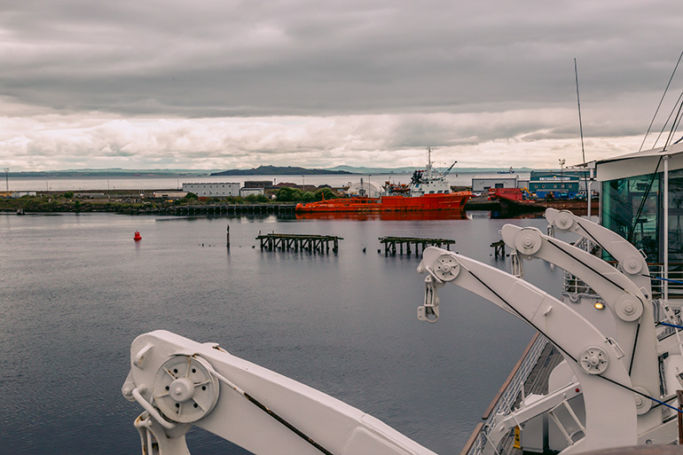 The views from Yacht Britannia - a still ocean and overcast sky.  Ships in the background and parts of the Yacht visible on the picture.