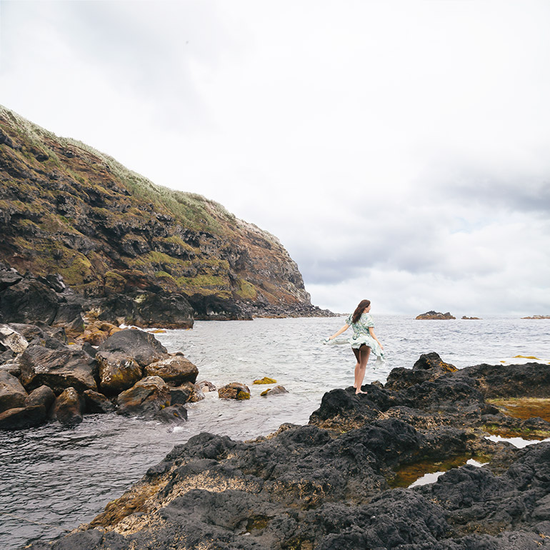 A woman (me) stands on a rock in Ponta De Ferraria.  In the background, sea, cloudy skies and sea cliffs.