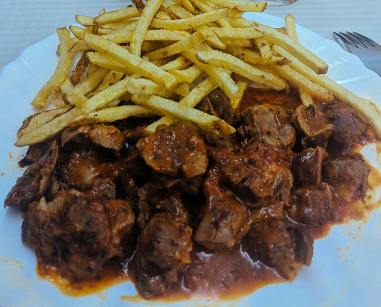 A plate with cooked meat, sauce and french fries.