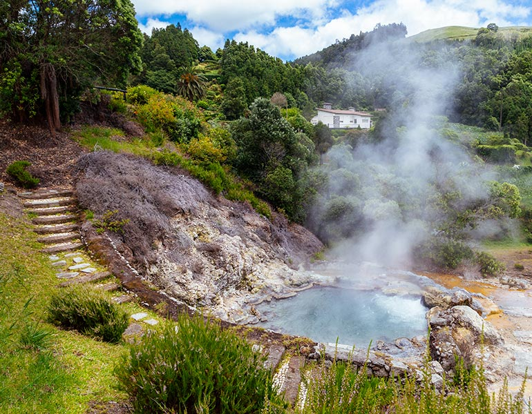 Smoke rises from a volcanic hot spring, and old stairs lead to the hot spring pool.  In the background a small white home.  Trees and grass surround the hot spring.