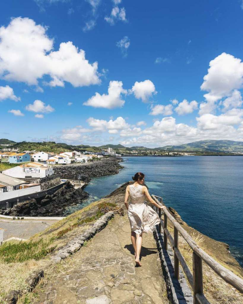 A brunette woman walking towards the ocean in Sao Roque, Sao Miguel.