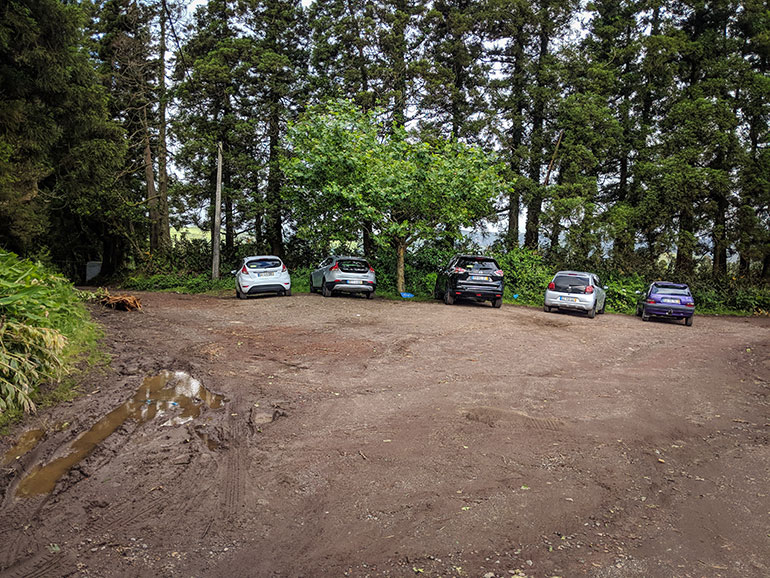 Lagoa Do Congro, Sao Miguel, Azores, Portugal. a group of vehicles parked in a dirt parking lot, surrounded by trees.