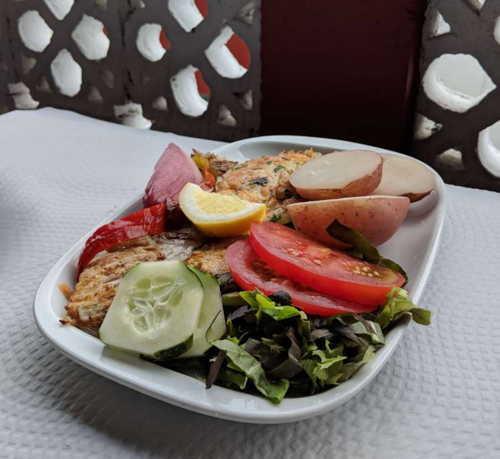 A plate with fish and vegetables on a white table.