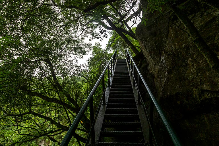 Metal stairs lead up to the top of the waterfall.
