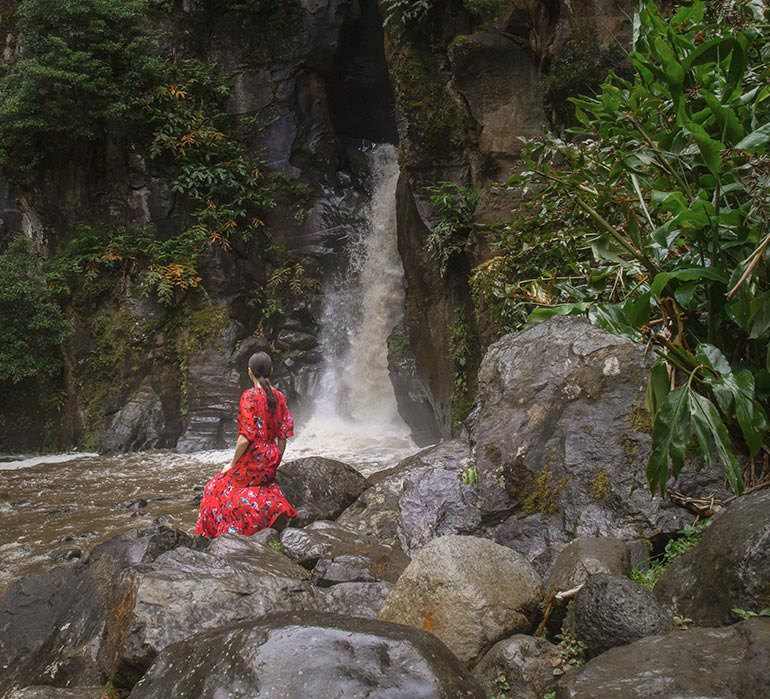 A woman (me) sits in front of a waterfall, on rocks.  Sao Miguel Azores, Portugal
