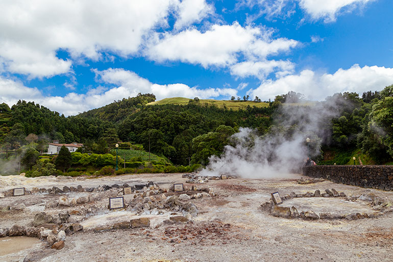 Large volcanic holes spread over the ground. Some emanate smoke. The wholes are surrounded by small rocks and some have signs that are illegible. In the background, hills and trees. Bright sky overhead.