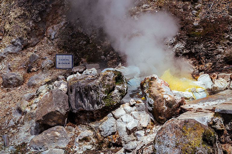Caldeiras Vulcanicas, Sao Miguel, Azores. Smoke eminates from a caldera. Yellow colored water erupts from the hole and smoke billows. An illegible sign shows the name. The Caldera is surrounded by rock.