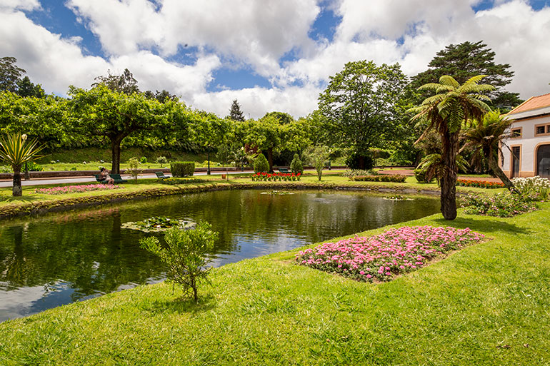 Caldeiras Vulcanicas, Caldera in Furnas, Sao Miguel, Azores A large reflective pool of water in a garden, surrounded by orderly trees and flowers.  In the background part of a large Mediterranean building.