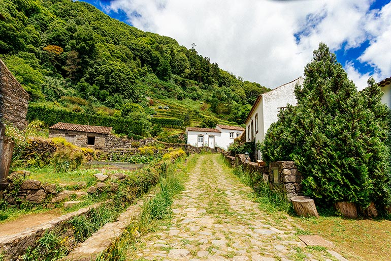 An abandoned white home in the village of Sanguinho at the end of a cobblestone road overgrown with grass.