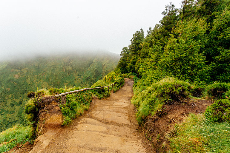 A path partially covered in fog in Miradouro Da Boca Do Inferno.