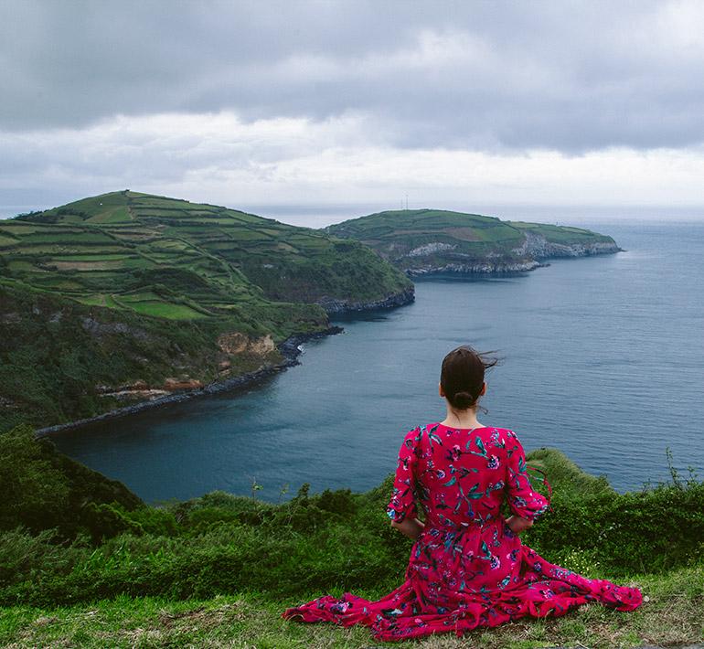 A woman sits in Miradouro De Santa Iria, behind her a landmass and the ocean.
