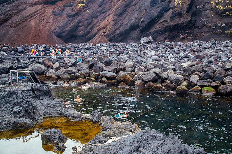 Ponta Da Ferraria, Sao Miguel, Azores, Portugal. A natural pool surrounded by rock.  In the pool several people.  Other people are standing around the pool on the rocks.