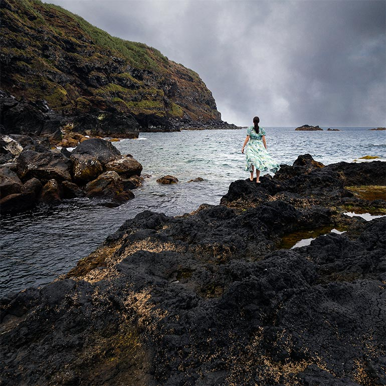 Ponta Da Ferraria, Sao Miguel, Azores, Portugal. A woman (me) stands on a rock facing the sea. Dramatic cloudy skies overhead and a green cliff in the distance.
