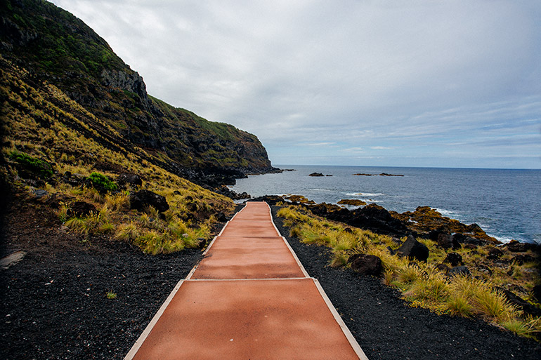 A red pathed path amidst volcanic rock on the shore.  Grass grows between some of the rock, and the sea is in the distance.  Ponta Da Ferraria - Sao Miguel Azores.