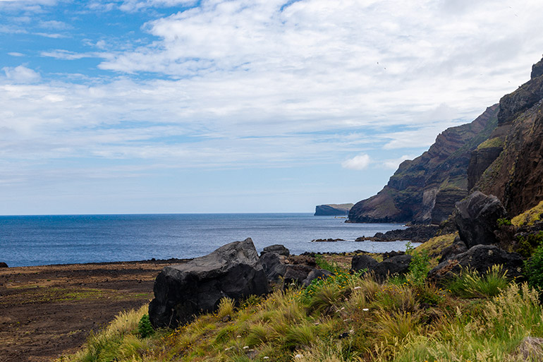 Ponta Da Ferraria, Sao Miguel, Azores, Portugal.  Cliffs in the background and a volcanic beach covered with grass in the foreground.  The sky is bright with mid day sun.