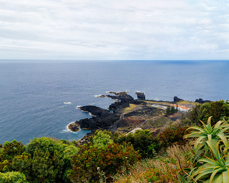 Ponta Da Ferraria, Sao Miguel, Azores, Portugal.  A shot taken from above.  Below, grass and trees and a rocky beach with a small home.  The beach is surrounded by the sea.