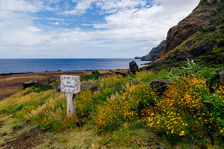"""An old pretty sign that says """"Ilha Rue Sabrina.  In the foreground flowers, grass and the sign, in he background cliffs, the sea and a bright sky, as seen in Sao Miguel Azores"""