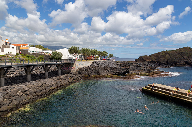 A swimming pier on one side of the picture, and a pathway on the other side.  Some homes in the background, and a sea cliff in the distance.  A bright, sunny day.  Seen in Forno Da Cal, Sao Miguel Azores