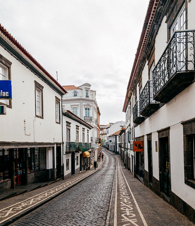 A peaceful, narrow cobble stone street in Ponta Delgada.  15th century road adapted for 21st century life, with narrow walkways on the side of a narrow road.  The row homes lining the streets are white and many sport an  authentic medieval charm.