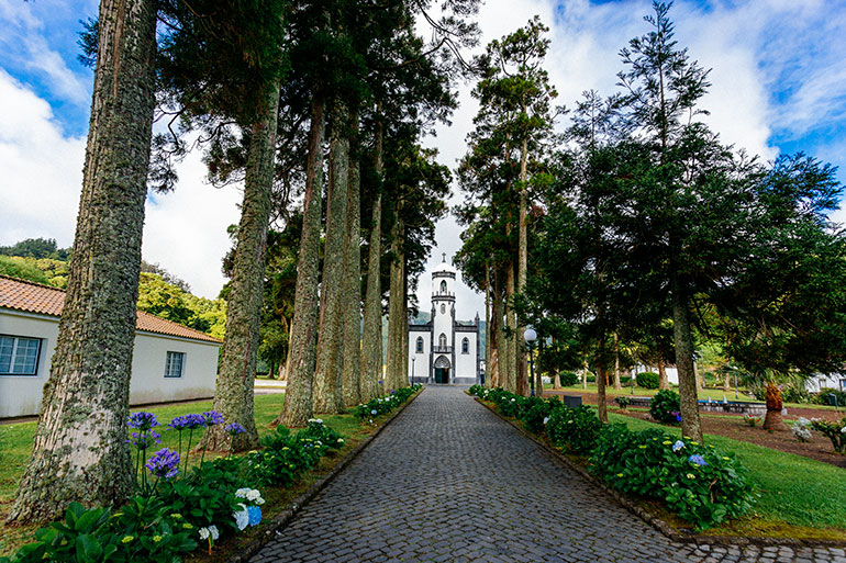 A white church in Sete Cidadesvillage at the end of a tree lined paved path.