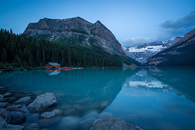 A cabin on the shores of Lake Louise during sunrise.