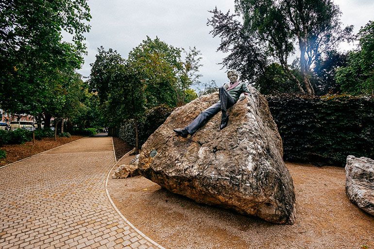 The statue of Oscar Wilde, resting on a rock.