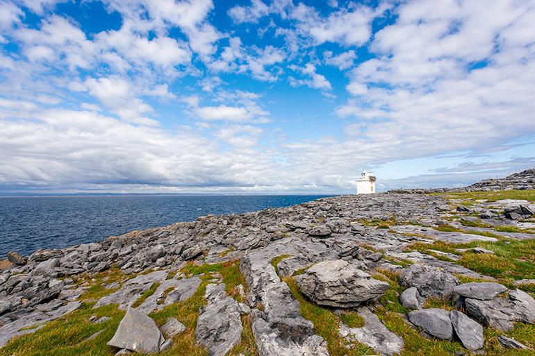 The blackhead lighthouse stands in isolation on a typical Burren landscape.