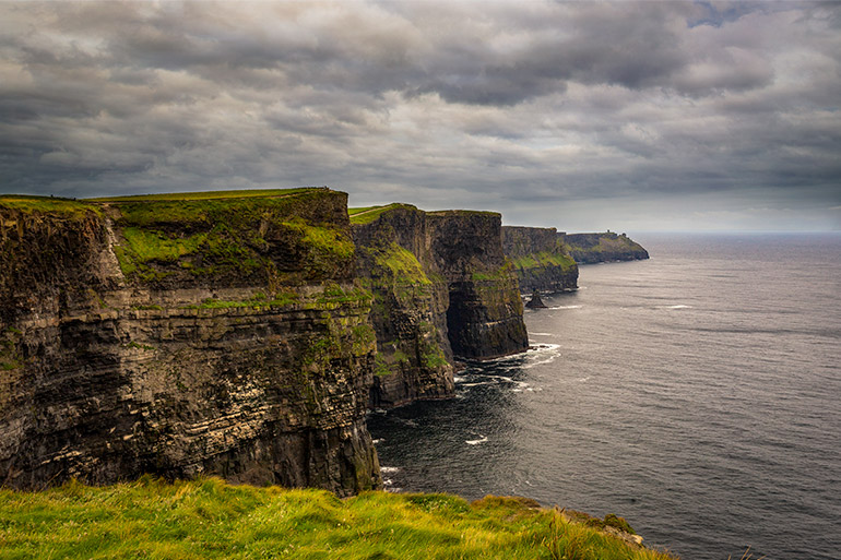 The dramatic cliffs of Moher under a cloudy sky.